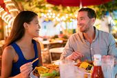 Couple eating hamburgers at outdoor restaurant terrace happy tourists on summer vacation. Florida tr poster