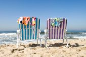 image of skinny-dipping  - Two beach chairs with bathing suits draped over them insinuate a couple is out for a nude dip in the cool ocean.