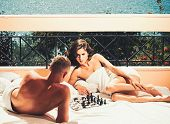Attractive Couple Play Chess On Terrace On Sunny Day. Couple In Love Play Chess On Balcony, Nature A poster