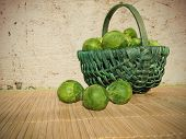 picture of cruciferous  - A green basket of fresh green brussels sprouts outside in the sun against an old stone wall - JPG