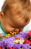 Cute Baby With A Bunch Of Flowers. poster