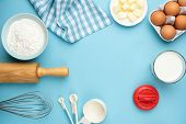 Baking Ingredients On Blue Background. Rolling Pin, Flour, Eggs, Butter, Measuring Spoons And Other  poster