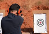 stock photo of shoot out  - Man shooting at a target on an outdoor shooting range - JPG