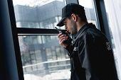 Handsome Guard In Black Uniform Talking On Walkie-talkie poster