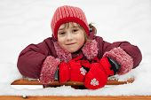 image of ruddy-faced  - Little girl in a knitted hat leaned on the bench - JPG
