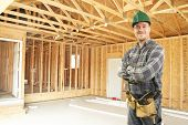 image of 2x4  - Construction worker standing in new home framed garage - JPG