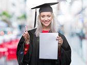 Young blonde woman wearing graduate uniform holding degree over isolated background surprised with a poster