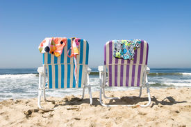 image of skinny-dip  - Two beach chairs with bathing suits draped over them insinuate a couple is out for a nude dip in the cool ocean.