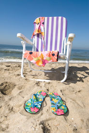 image of skinny-dip  - A beach chair with bathing suit draped over them and thongs in the sand insinuate a beachgoer is out for a nude dip in the cool ocean - JPG