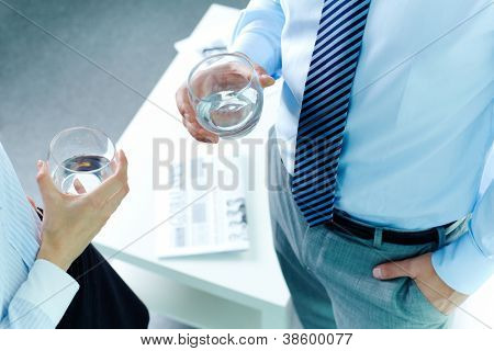 Photo of business partners hands holding glasses with water