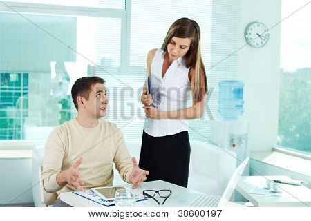 Image of confident businessman looking at pretty colleague while explaining his idea