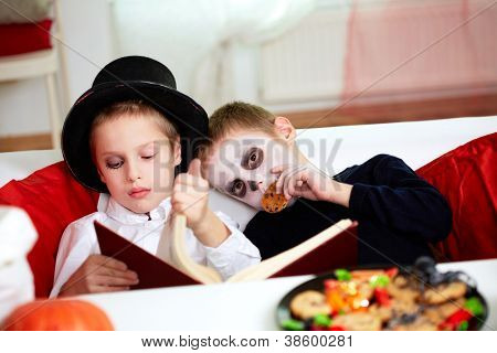 Photo of two eerie boys reading and eating cookies on Halloween day