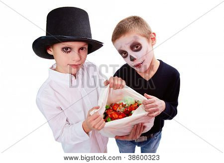 Photo of two eerie boys with sack of Halloween treats looking at camera