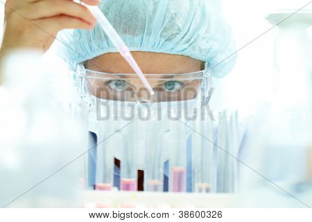 Chemist testing sample of liquid in laboratory