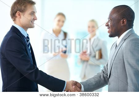 Portrait of happy leaders handshaking and two females applauding on background
