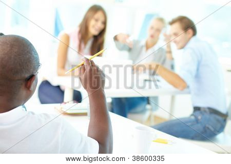 Rear view of African guy holding pencil with group of students working on background
