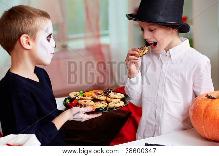 Photo of two eerie boys eating cookies on Halloween day