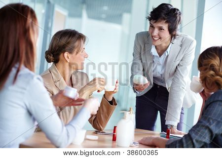 Image of four businesswomen talking about beauty products at break