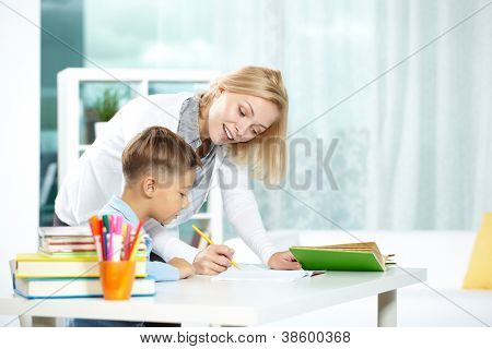 Portrait of smart tutor with pencil correcting mistakes in pupil�?�¢??s notebook