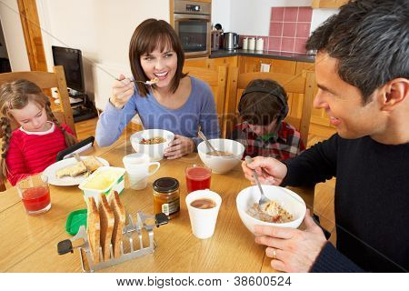 Family Eating Breakfast Together In Kitchen Whilst Children Play With Gadgets