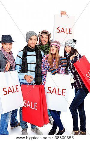 Grupo de jovens alegres com sacos de compras. Isolado sobre o fundo branco.