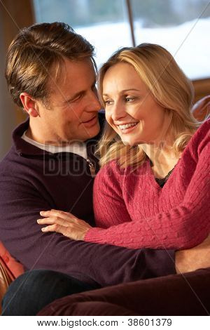 Middle Aged Couple Chatting On Sofa In Chalet With Winter View