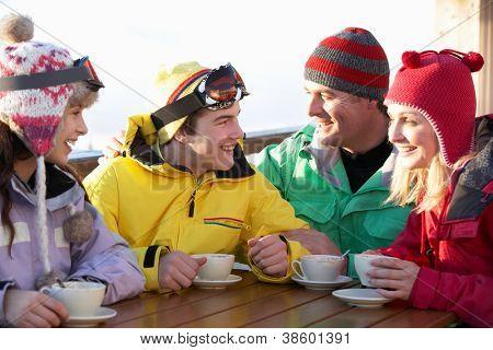 Teenage Family Enjoying Hot Drink In Cafe At Ski Resort