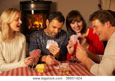 Group Of Middle Aged Couples Playing Cards Together