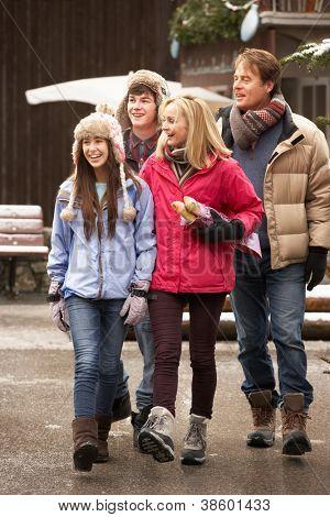 Família de adolescente andando em rua de cidade Snowy na estância de esqui