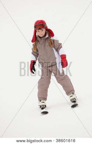 Young Girl Skiing Down Slope On Holiday In Mountains