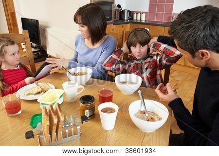 Parents Taking Away Gadgets From Children Whilst Eating Breakfast Together In Kitchen