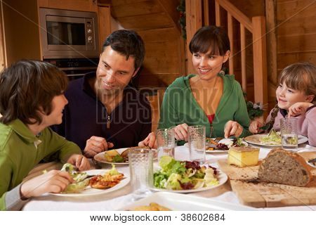 Family Enjoying Meal In Alpine Chalet Together
