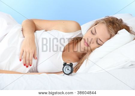 young beautiful woman sleeping on bed with alarm clock on blue background