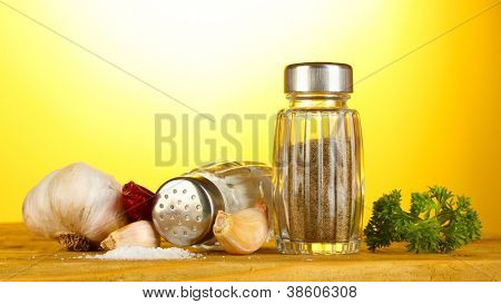 Salt and pepper mills, garlic and parsley on wooden table on yellow background