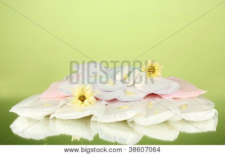 various types of sanitary pads and tampons on green background close-up