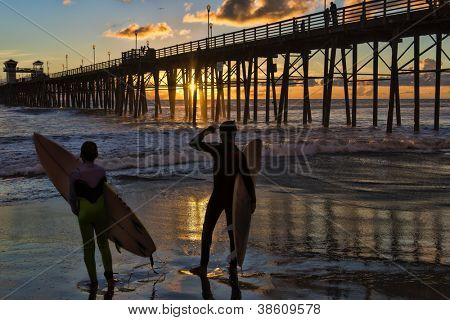 Surfers at sunset in Oceanside, California admire the sun setting through the old wooden pier.