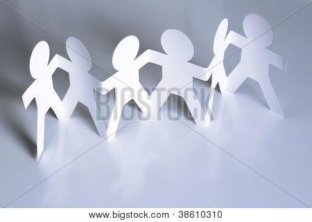 Team of six paper doll people holding hands. Teamwork concept
