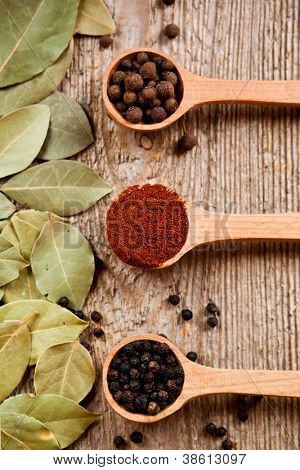 three kinds of pepper in wooden spoons and bay leaves on rustic wooden background