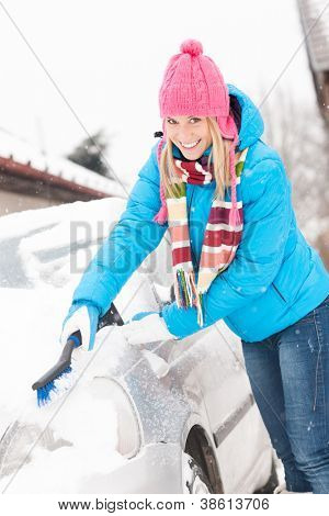 Woman cleaning car hood of snow brush happy winter wiping
