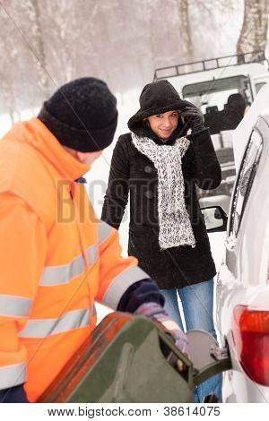 Man filling gas tank car breakdown woman winter snow assistance