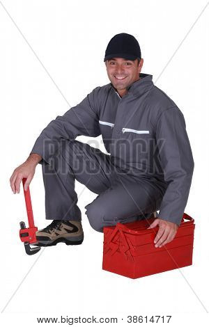 Plumber crouching by his tool box