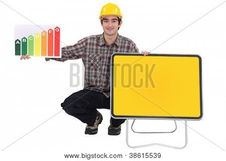 Tradesman squatting next to a traffic sign and holding an energy efficiency rating sign
