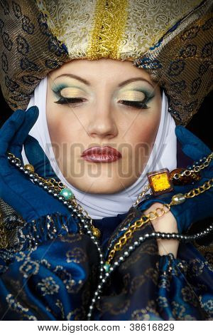 Beautiful young woman in colorful stylized medieval costume