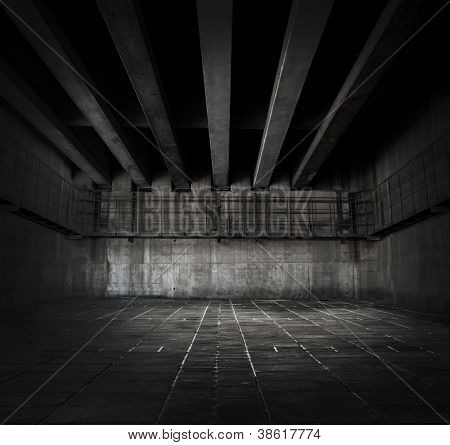 Dark stone and concrete space with tiled floor and ceiling of concrete beams.