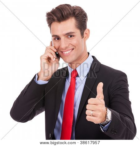 smiling young business man talking on the smart phone and making ok gesture. Isolated on white background