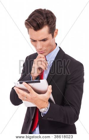 serious young business man focused on reading something on his tablet pad