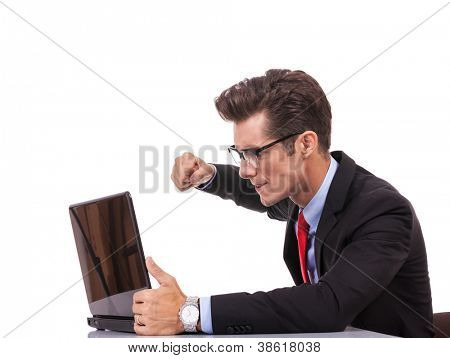 side view of an angry business man at his laptop, on gray background