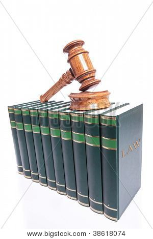 wooden judge gavel and sound block on top of a stack of books
