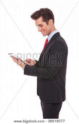 Side view of smiling business man using his tablet computer against a white background