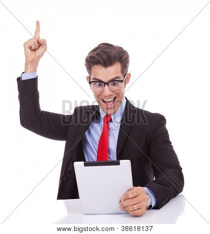 young business man wearing glasses screaming of joy while reading the good news on the tablet pad